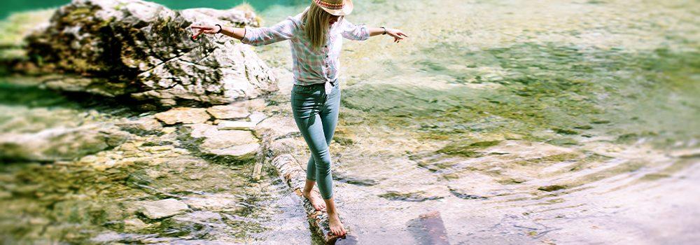 Immer schön die Balance halten! Frau im Urlaub hält das Gleichgewichtauf einem Baumstamm in einem wunderschönen See