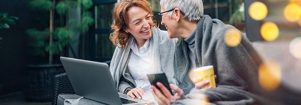 Über Geld spricht man nicht? Wir schon! Zwei charmante, reifere Frauen lachen zusammen wärend sie draußen sitzen und in Decken gekuschelt auf ihr Laptop und ihr Handy schauen und entspannt über Finanzen reden