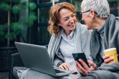 Online-Banking: Zwei charmante, reifere Frauen lachen zusammen wärend sie draußen sitzen und in Decken gekuschelt auf ihr Laptop und ihr Handy schauen