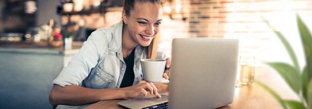 Finanzwissen - Packen wir es an! Junge Frau, die interessiert und mit Eigeninitiative am Laptop über Finanzen recherchiert
