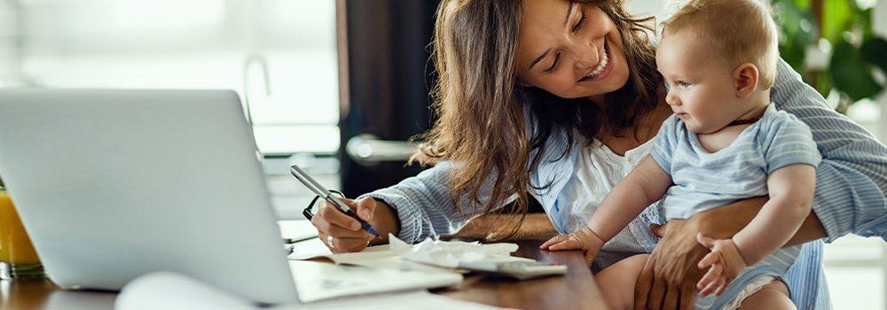 Rentenlücken: Die Finanzen im Griff! Junge Mutter hält ihren Sohn auf dem Schoß während sie sich am Laptop Finanzwissen sucht, um ihre Altersvorsorge selbst zu planen