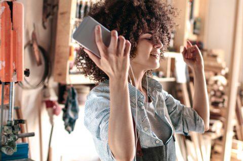 Existenzgründung - Mach dein Ding! Junge Frau, selbstständig, zufrieden und unabhängig, hört Musik in ihrer Werkstatt