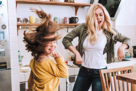 Powerfrau, alleinerziehend! Alleinerziehende Frau, die fröhlich mit ihrer Tochter durch die Küche tanzt