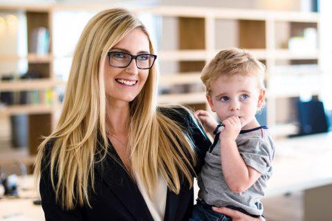 Zurück in den Job: Mutter und Karrierefrau stellt ihren kleinen Sohn nach der Elternzeit auf der Arbeit vor