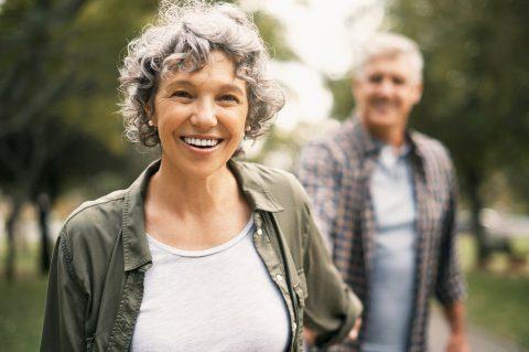 Altersvorsorge - Da geht noch was! Reife Dame hält ihren Ehpartner an der Hand und geht optimistisch in die Zukunft